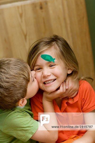 Zwei Kinder küssen.