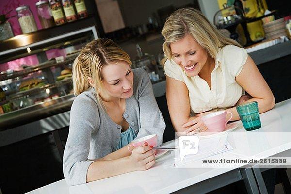 Zwei Frauen mit einem Geschäftstreffen und eine Tasse Kaffee in einem CafÈ Schweden.