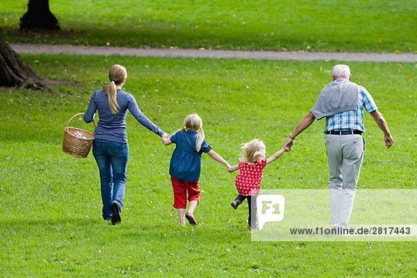 älterer Mann Frau und Kinder gehen für ein Picknick im Park Schweden.