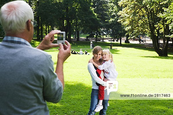 Woman senior man and girl taking photographs in the park Sweden.