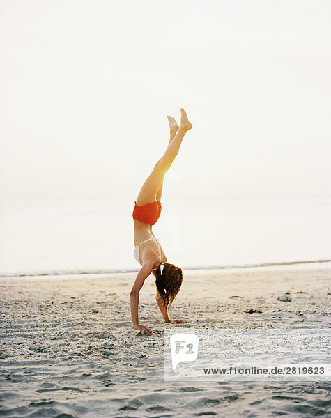 Eine skandinavische Frau tun einen Handstand am Strand.