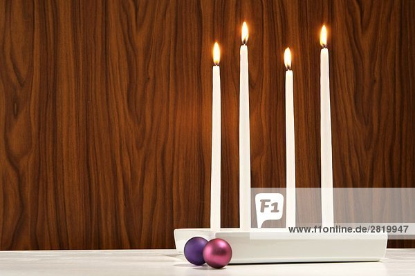 Four candles burning near baubles