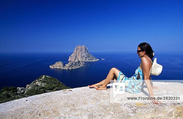 Frau sitzt auf einer Klippe auf der Suche auf See  Ibiza  Balearen Inseln  Spanien