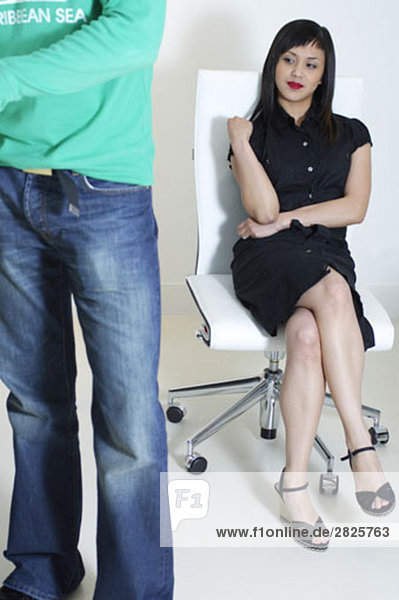 young asian executive looking at behind of male colleague