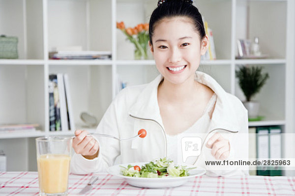 portrait of young japanese girl eating salad