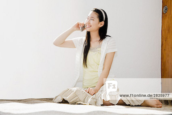 Ganzkörper-Porträt der jungen Japanerin sitzen auf Boden sprechen auf Handy
