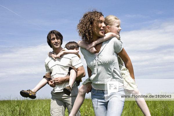 junge Eltern ihren Kindern Huckepack ride