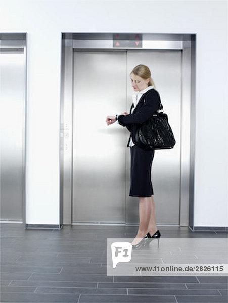 junge geschäftsfrau vor Aufzug Blick auf ihre Watch Stand