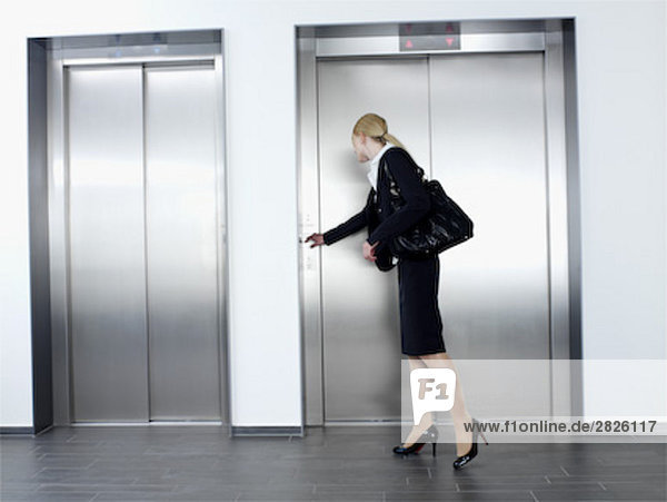 junge geschäftsfrau standing in front of Elevator Lift Knopfdruck