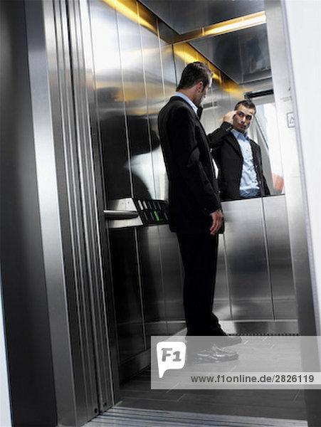 young Businessman im Aufzug Überprüfung sein Aussehen in den Spiegel