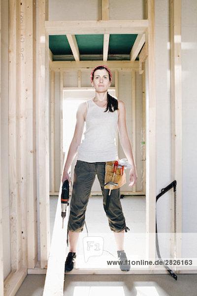 Ganzkörper Portrait einer jungen Frau standing in Tür des Hauses im Bau