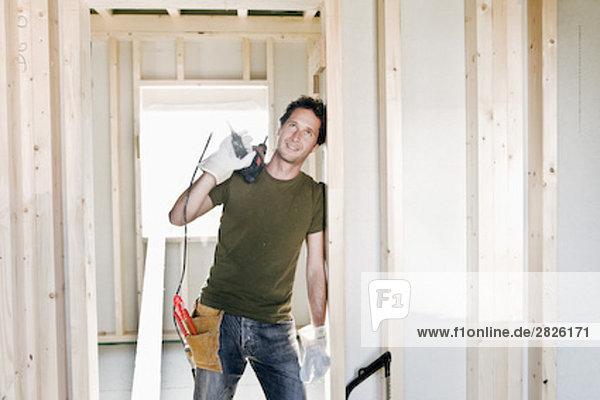 stehend bauen Portrait Mann Wohnhaus Tür unterhalb jung