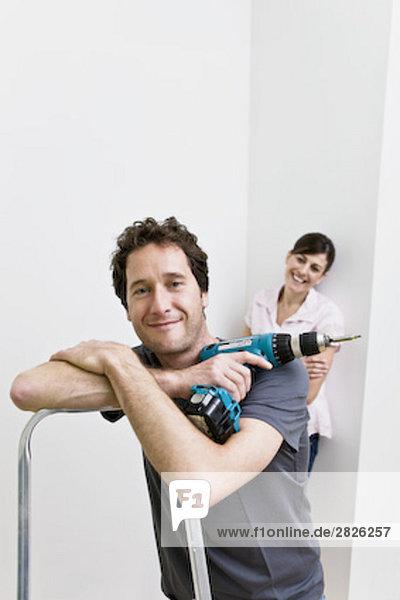 Portrait Mann halten Schraubenzieher jung schnurloses Telefon Eigentumswohnung neues Zuhause
