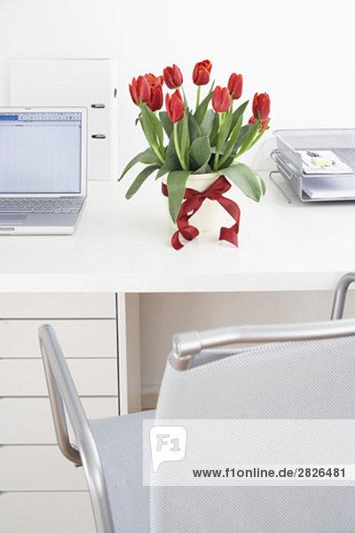 Stillleben mit Bündel von rote Tulpen auf Schreibtisch