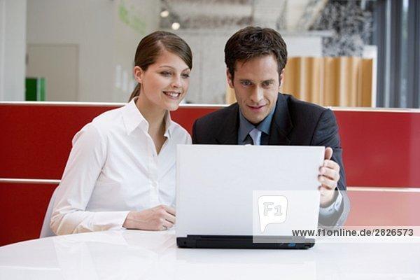 zwei Geschäftsleute arbeiten bei Laptop zusammen