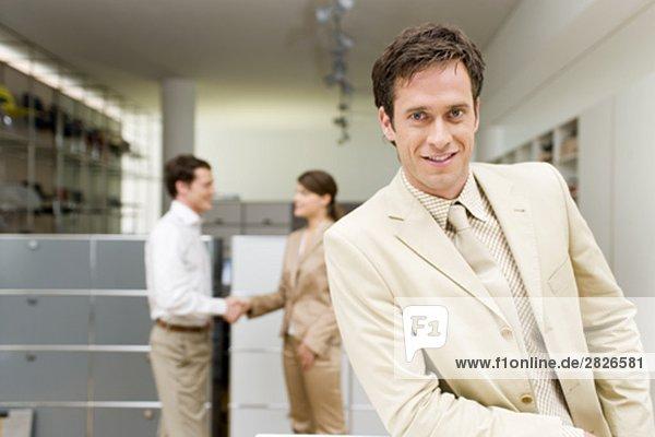 Portrait der Geschäftsmann mit zwei Kollegen Händeschütteln im Hintergrund