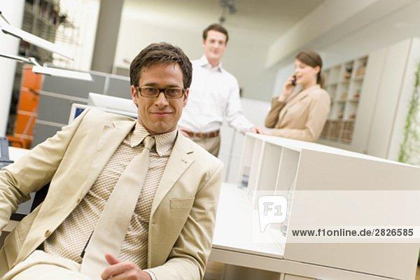 Portrait des Kaufmanns an Schreibtisch im Büro sitzen