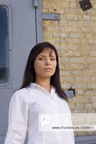 portrait of young businesswoman in front of wall