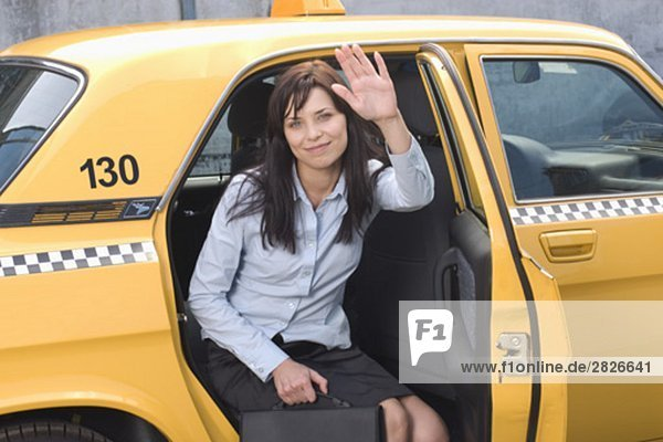 portrait of young businesswoman leaving yellow taxi