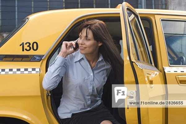portrait of young businesswoman leaving yellow taxi talking on mobile phone