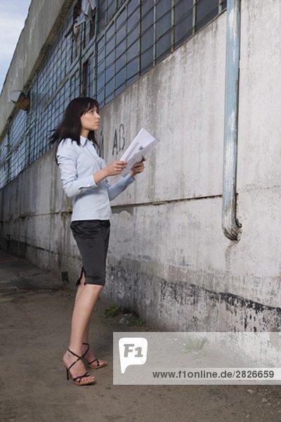 junge geschäftsfrau vor Gewerbehalle Plan in Händen halten Stand