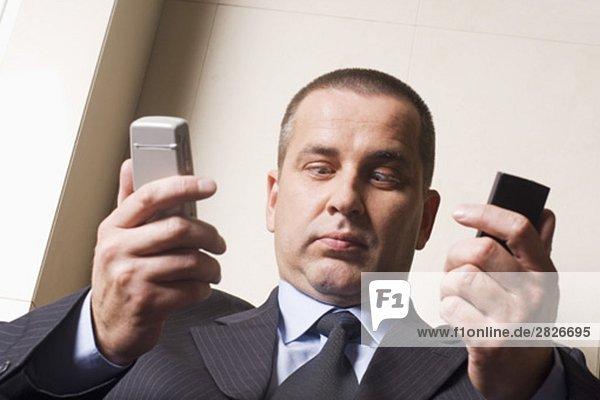 Headshot of Cross-Eyed mündig Geschäftsmann mit zwei Handys