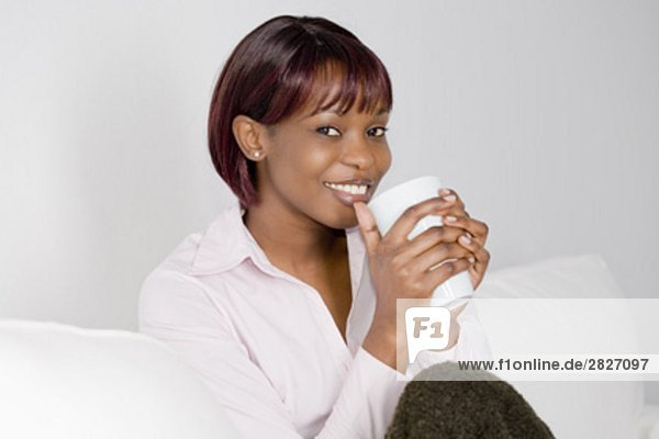 portrait of young black woman sitting on sofa and holding cup