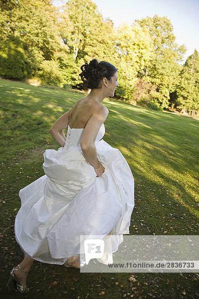 Mittelalte Braut die in Park rennt
