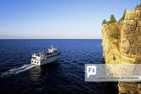 Eine Tour Boot Köpfe aus für eine Sonnenuntergangskreuzfahrt auf Georgsbucht entlang der Klippen von der Niagara-Schichtstufe in Bruce Peninsula National Park  Ontario  Kanada.