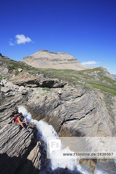 Wanderer Sitzung von einem Wasserfall am Dolomit Creek in den kanadischen Rocky Mountains  Banff-Nationalpark  Alberta  Kanada.