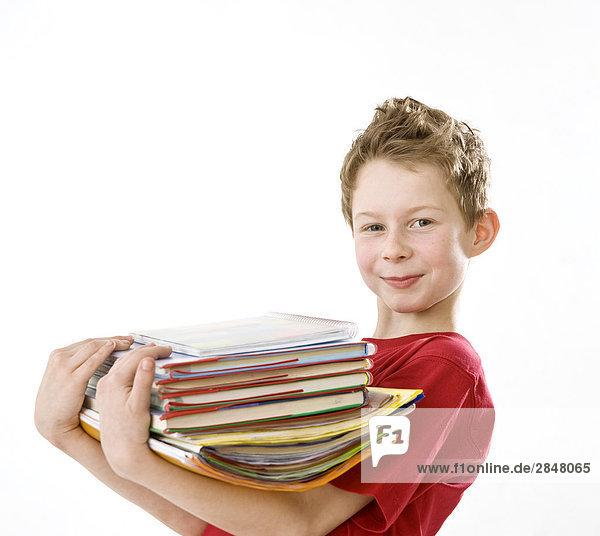 Junge hält Stapel von Büchern