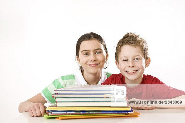 Mit ihrem Bruder in der Nähe von Bücher lächelnd mädchen