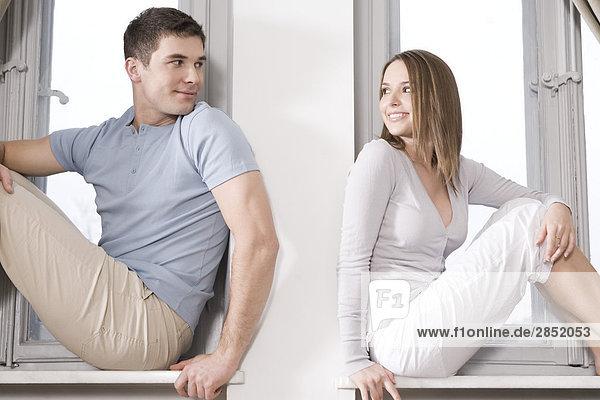 paar sitzend neben Fenster