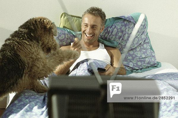 Mann spielt mit Hund im Bett