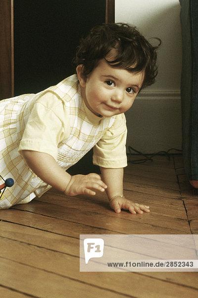 Little girl crawling on floor