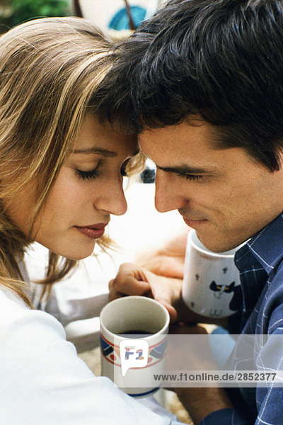 Paar  das die Stirn über dem Kaffee berührt.
