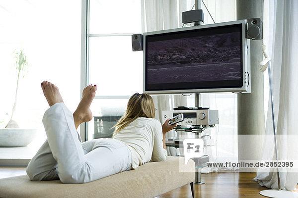 Frau auf Chaiselongue liegend  Flachbildschirm-Fernsehen mit Surround-Sound