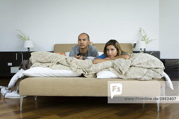 Paar liegt im Bett und schaut fern.