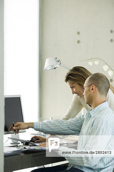 Paar im Home-Office  gemeinsam auf den Computer schauen
