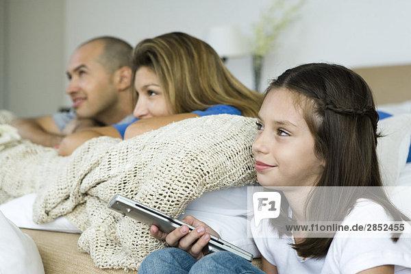 Familie beim gemeinsamen Fernsehen  Mädchen mit Fernbedienung