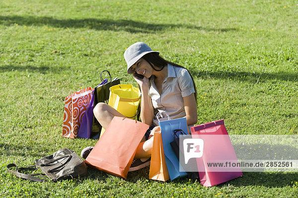 Junge Frau im Park sitzend  umgeben von Einkaufstaschen
