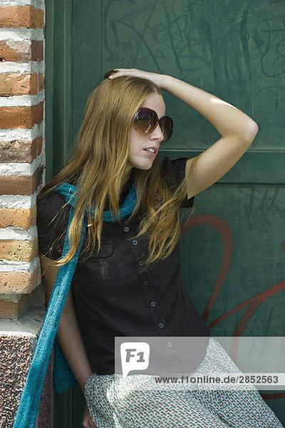Junge Frau mit erdbeerblondem Haar mit Schal und Sonnenbrille  Hand auf Kopf