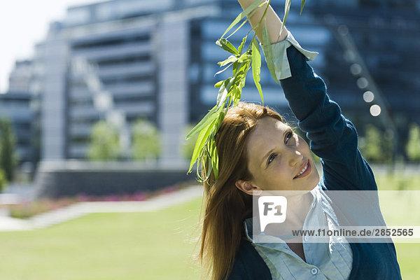Junge Frau steht im Freien  berührt einen Ast  schaut weg