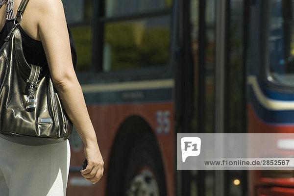 Frau wartet vor dem Bus  abgeschnitten