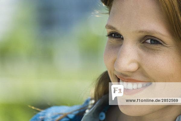 Junge Frau schaut weg  lächelnd  Portrait