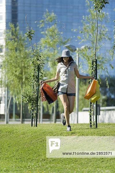 Junge Frau geht mit Einkaufstaschen im Park spazieren