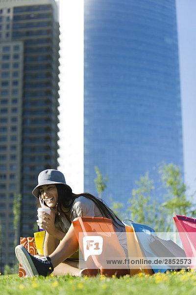 Junge Frau sitzend im Park mit Einkaufstüten  schlürfend Getränk mit Strohhalm