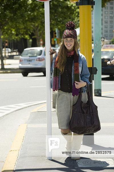 Junge Frau in trendiger Kleidung auf dem Bürgersteig stehend  Ganzkörperporträt