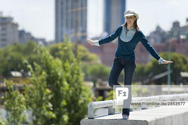 Junge Frau in trendiger Kleidung auf einem Bein auf dem Sims stehend