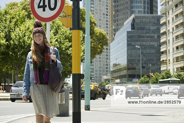 Trendige junge Frau geht die Stadt entlang